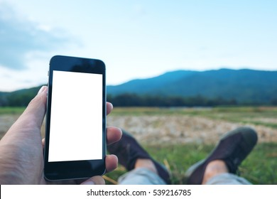 Mockup image of lay down and hand holding black mobile phone with blank white screen in field and green nature mountain under blue sky , feeling relax and rest with black canvas shoes