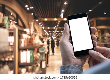 Mockup image, man hands using blank white screen mobile smart phone with supermarket background, digital banking, internet payment, e-commerce concept