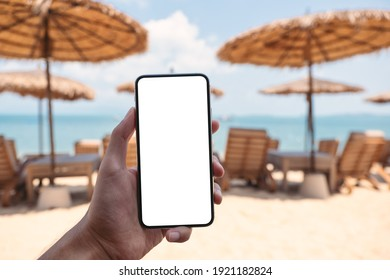 Mockup image of a man holding mobile phone with blank desktop screen while sitting on the beach - Shutterstock ID 1921182824