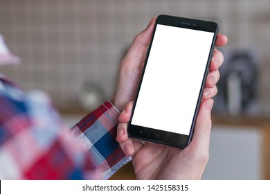 Mockup image: man looking at black smartphone with white blank screen. Close up view of man hands with smart phone mobile device. Mock up, copyspace, template and technology concept