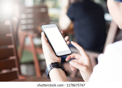 Mockup image of a man's hand holding white mobile phone with blank black desktop screen on thigh in cafe
