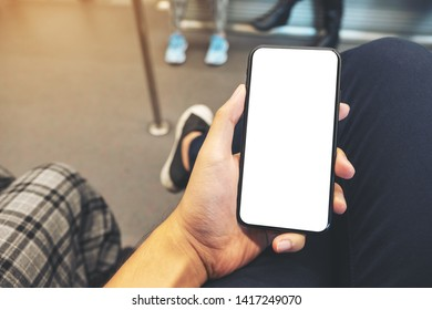 Mockup image of a man's hand holding black mobile phone with blank screen in subway