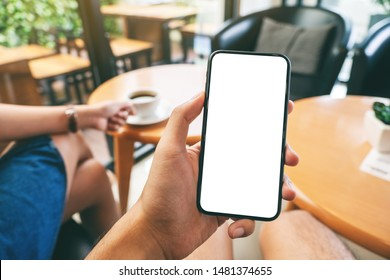 Mockup image of a man's hand holding black mobile phone with blank white screen with woman drinking coffee in cafe