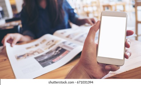 Mockup image of a man's hand holding white mobile phone with blank screen in modern cafe and blur woman reading newspaper in background