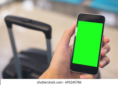 Mockup image of a man's hand holding and using black mobile phone with blank green screen with black baggage in airport