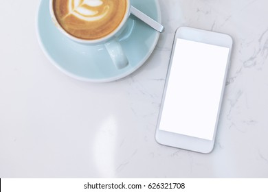 Mockup image of mobile phone with blank white screen and blue coffee cup with latte art on marble table in cafe