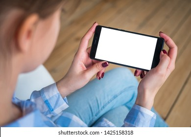 Mockup image - over shoulder view: woman hands holding black smartphone with white blank screen in home interior with floorboards. Mock up, copyspace, template, entertainment and technology concept