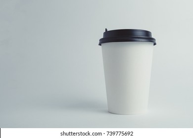 Mockup image of paper cup with cap on clean bacground