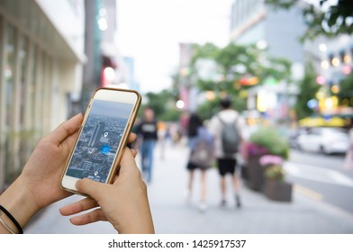 Mockup image, people lifestyle, GPS pin and map satellite navigator apps concept. Woman using mobile smart phone searching location via mobile application with blurred background of people in the city