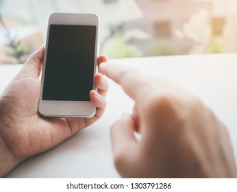Mockup image of woman hand holding and touching white mobile phone with blank screen black colour smartphone