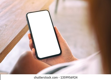 Mockup image of a woman holding black mobile phone with blank white screen in cafe