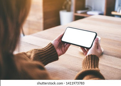 Mockup image of a woman holding black mobile phone with blank desktop screen horizontally with coffee cup on the table