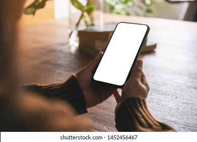 Mockup image of woman holding black mobile phone with blank desktop screen on wooden table