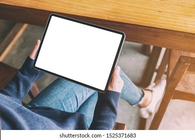 mockup image of a woman holding black tablet pc with blank white screen while sitting in cafe