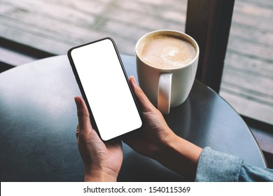 Mockup image of a woman holding black mobile phone with blank screen with coffee cup on the table