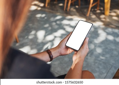 Mockup image of a woman holding black mobile phone with blank desktop screen