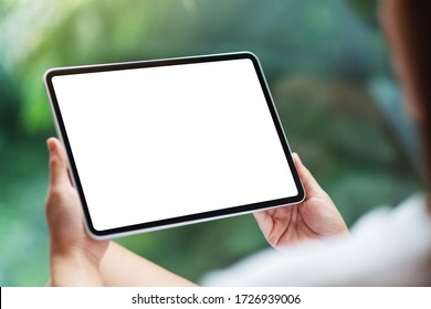 Mockup image of a woman holding black tablet pc with blank white desktop screen , green nature background