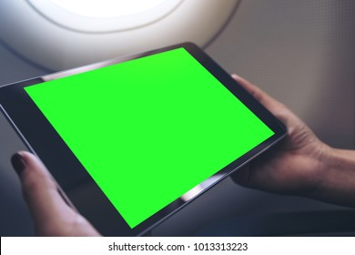 Mockup image of a woman holding and looking at black tablet pc with blank green desktop screen next to an airplane window