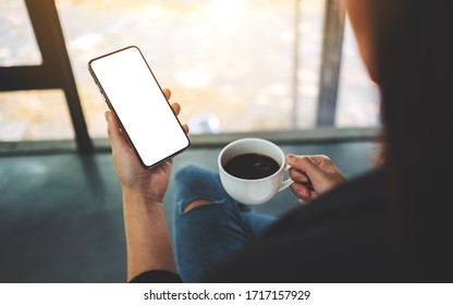 Mockup image of a woman holding mobile phone with blank screen while drinking coffee