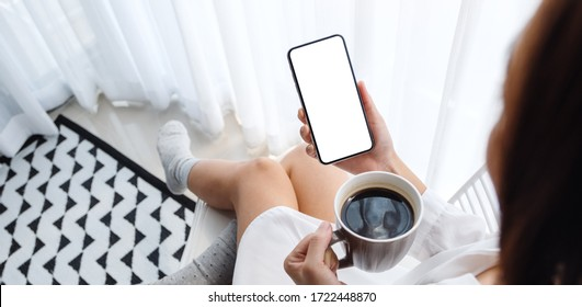 Mockup image of woman holding mobile phone with blank white desktop screen while sitting and drinking coffee in bedroom