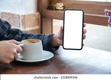 Mockup image of a woman holding and showing black mobile phone with blank white screen while drinking coffee