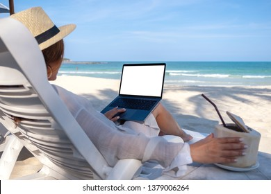 Mockup image of a woman holding and using laptop computer with blank desktop screen while laying down on beach chair and drinking coconut juice on the beach