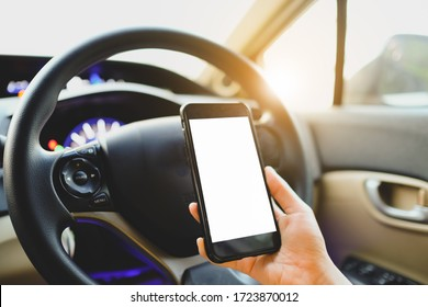 Mockup image of a woman holding and using mobile phone with blank screen while driver a car.