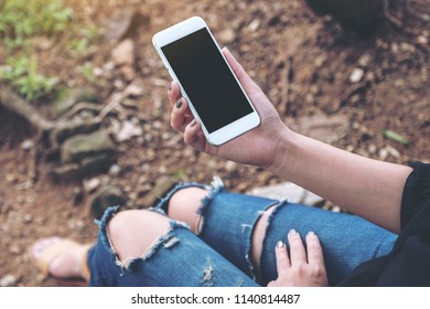 Mockup image of woman holding white mobile phone with blank desktop screen while sitting on the ground outdoor