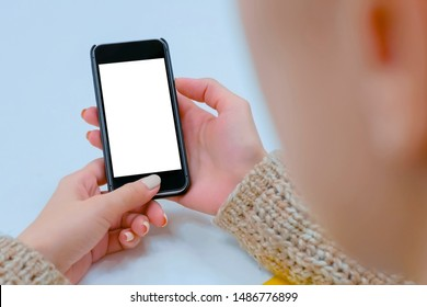 Mockup image: woman looking at black smartphone with white blank screen. Close up view of woman hands with smart phone mobile device. Mock up, copyspace, template and technology concept - mockup image