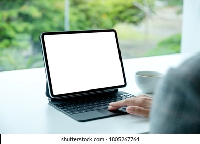 Mockup image of a woman touching on tablet touchpad with blank white desktop screen as computer pc in the office
