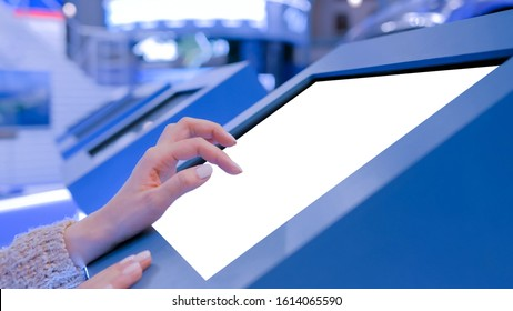 Mockup image - woman touching white empty interactive touchscreen display kiosk in dark room of modern technology museum. Mock up, template, scifi, education, futuristic and technology concept