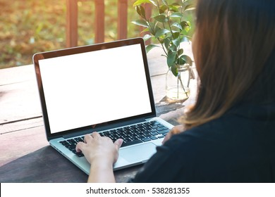 Mockup image of a woman using laptop with blank white screen on vintage wooden table in nature outdoor park