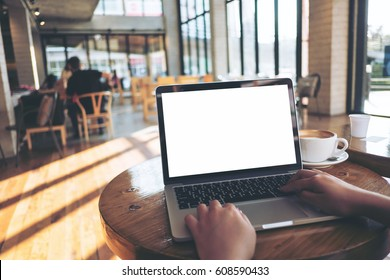 Mockup image of a woman using laptop with blank white screen on wooden table in modern loft cafe