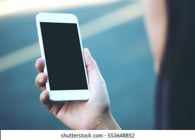 Mockup image of a woman using smart phone with blank black screen at outdoor