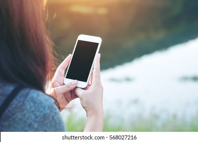 Mockup image of a woman using smart phone with blank black screen at outdoor and lake nature background