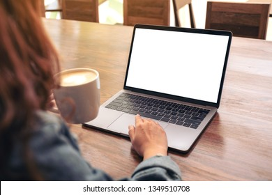 Mockup image of a woman using and touching on laptop touchpad with blank white desktop screen on wooden table while drinking coffee