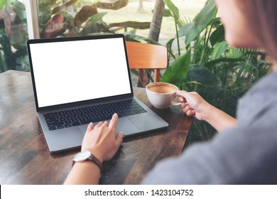 Mockup image of a woman using and touching laptop touchpad with blank white desktop screen while drinking coffee on wooden table