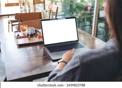 Mockup image of a woman using and touching laptop touchpad with blank white desktop screen on wooden table in cafe