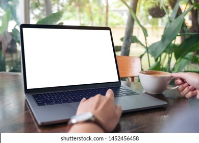 Mockup image of a woman using and touching laptop touchpad with blank white desktop screen while drinking coffee