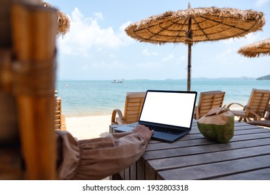Mockup image of a woman using and touching on laptop touchpad with blank desktop screen while sitting on the beach