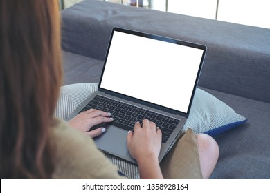 Mockup image of a woman using and typing on laptop keyboard with blank white screen while sitting in living room
