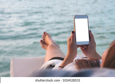 Mockup image of a woman using white mobile phone with blank desktop screen while lying by the sea