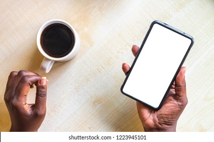 Mockup image of woman's hand holding white mobile phone with blank screen on thigh with wooden floor background in modern cafe