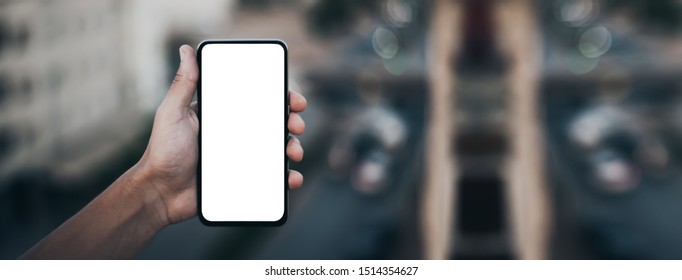 Mockup image of a woman's hand holding black mobile phone with blank desktop screen