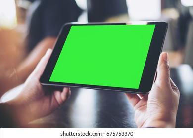 Mockup image of woman's hand holding black tablet pc with blank green screen in cafe with blur background