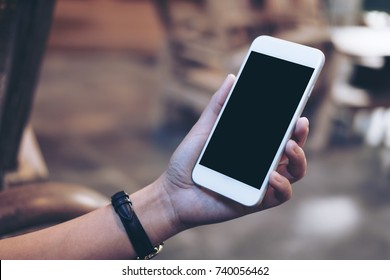 Mockup image of a woman's hand holding white mobile phone with blank black screen , concrete floor background
