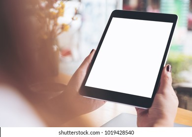 Mockup image of woman's hands holding black tablet pc with blank white desktop screen and laptop on wooden table in cafe