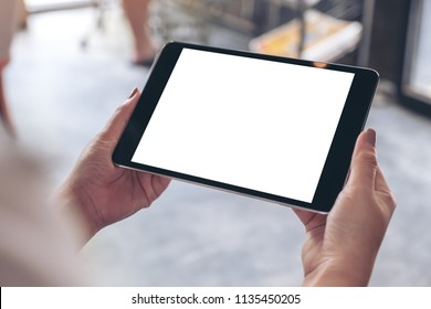 Mockup image of woman's hands holding black tablet pc with white blank desktop screen in cafe