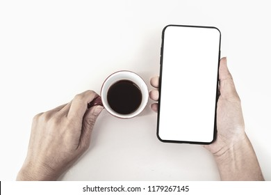 Mockup image of woman's hands holding black mobile phone with blank screen on white table and coffee cup in cafe
