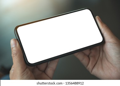 Mockup image of woman's hands holding black mobile phone with blank white screen horizontally in cafe